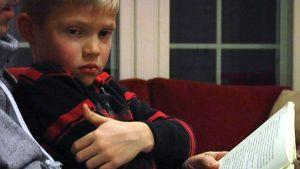 Adrian sitter i sin pappas famn och lyssnar noga