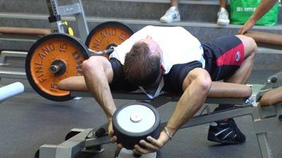 En ung man lyfter tyngder på gymmet.