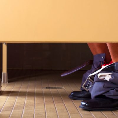 En person är på en allmän toalett. Bara byxbunten och skorna syns under båsen.