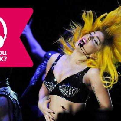 Lady Gaga blundar, är iklädd BH, har trådlös mikrofon vid munnen och slänger med huvudet bakåt, så håret står på ända.