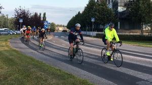En klunga cyklister i Borgå. Längst fram cyklar en man i svart och en man i gul jacka.