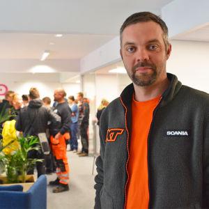 En man i orange arbetsuniform tittar in i kameran. Han står inne i ett rum och bakom honom finns många människor.