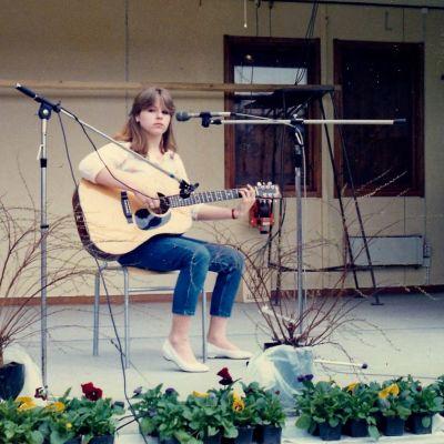 En ung Anneli Magnusson sitter på en stol på en scen med gitarr i handen. Mikrofoner står uppställda mot henne och hon ser rakt in i kameran.