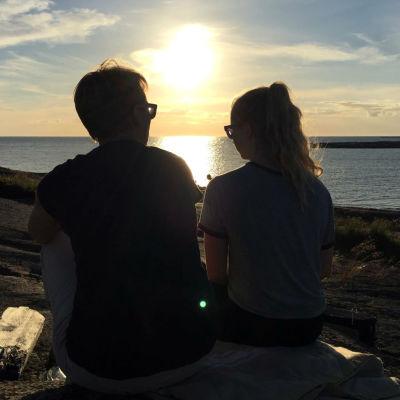 En mamma och en tonårsdotter sitter på klippa i solnedgången och pratar med varandra.