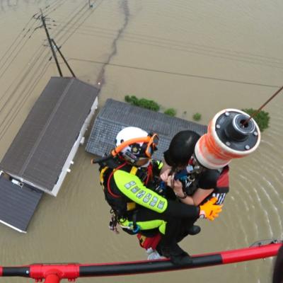 En räddningsarbetare hissar upp en invånare i en helikopter från ett översvämmat hus i prefekturen Saga i sydvästra Japan.