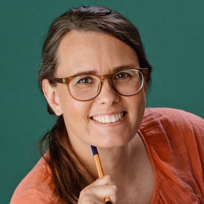 En kvinna med glasögon och långt hår. En penna vilar mot hennes haka.