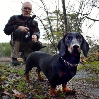 Bo Vilander framför en sjö tillsammans med sin svart-bruna tax.
