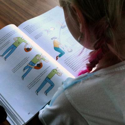 Tyttö lukee oppikirjaa