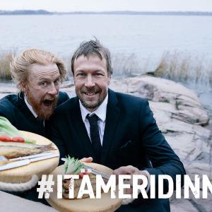 Peltsi ja Tom Nylund rannalla puvut päällä kala-annoksia tarjoillen