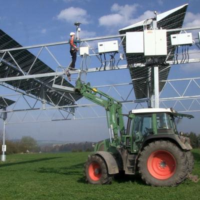 En traktor på en tysk åker med solpaneler högt ovanför marken. En man håller på med underhållsarbete.