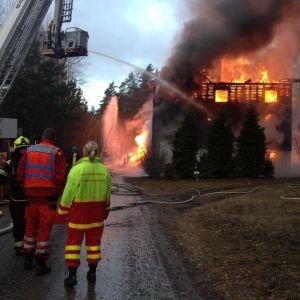 Räddningsmanskap arbetar vid ett brinnande hus.