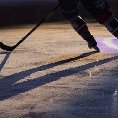 Kuvassa näkyy pelaajan jalat ja maila.