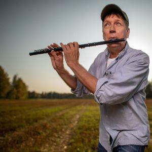 Pasi Hiihtola spelat flöjt på en åker