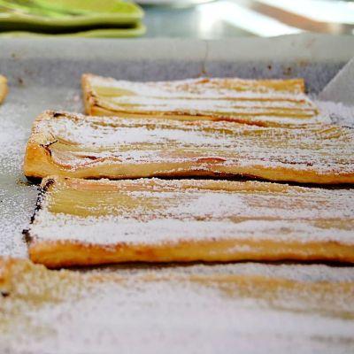 En bakplåt med nybakade rabarberpajer. Pajerna är bakade på smördegsplattor med tunnt hyvlade rabarberstjälkar och ett ordentligt lager med pudrat florsocker.