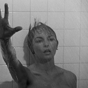 Nainen (Janet Leigh) nojaa suihkussa kaakeliseinään ja kurottaa kädellään kohti kameraa. Kuva elokuvasta Psyko.