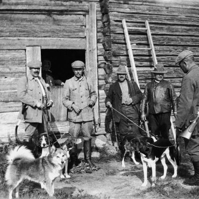 Miehiä lahdössä koirien kanssa metsälle.
