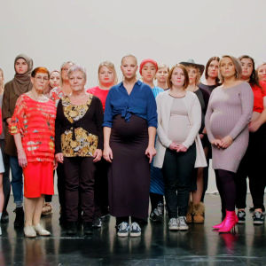 Kolmekymmentä eri-ikäistä naista studiossa katsoo kameraan.