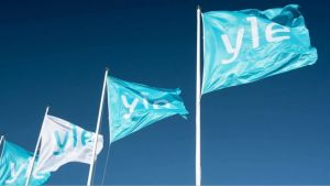 White and turquoise Yle flags against a blue sky.