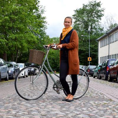 Inka-Maria Pulkkinen står på en kullerstensgata med sin cykel.