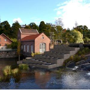 Ett bildmontage som visar hur fisktrappan i Svartån i Billnäs kan se ut. Stor betongkonstruktion mitt i forsen. På stranden gamla rödtegelbyggnader.