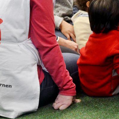 Pelastakaa Lapset ry:n vapaaehtoistyöntekijä istuu lapsen kanssa lattialla.