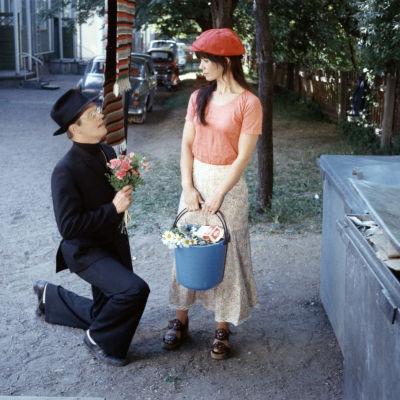 Kuva elokuvasta Mies joka ei osannut sanoa ei. Antti Litja polvistuneena pihalla Kirsti Wallasvaaran edessä.