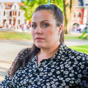 Kaisa Augusta Hansén-Suckow sitter på en parkbänk i solen och tittar in i kameran.