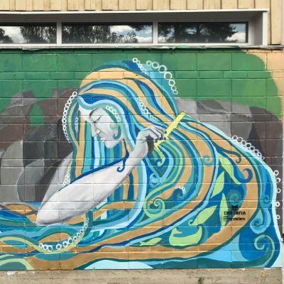 Vedenneito-muraali, jossa vedenneito kampaa valtoimenaan olevia hiuksiaan.