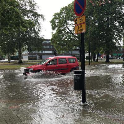 En bil kör genom cirka 30 centimeter djupt vatten i centrum av Raumo.