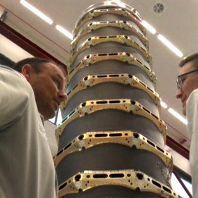 Två män står bredvid minisatelliter.