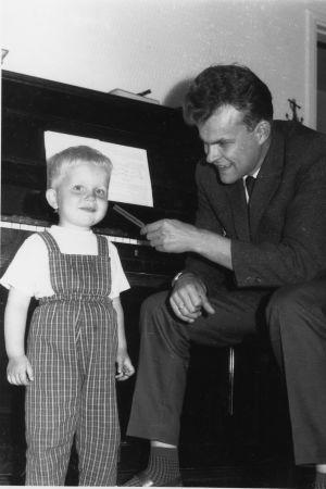 Sören Lillkung som barn tillsammans med sin pappa vid ett piano.