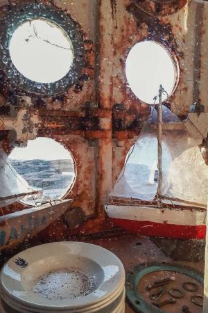 Tuplaikkuna, ulompi ikkuna koostuu metalliritilästä, jossa pyöreitä aukkoja. Välitilassa pino lautasia ja purjeveneen pienoismalli.