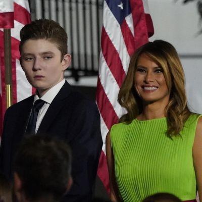 Barron Trump bredvid sin mamma Melania Trump. I bakgrunden applåderande politiker.