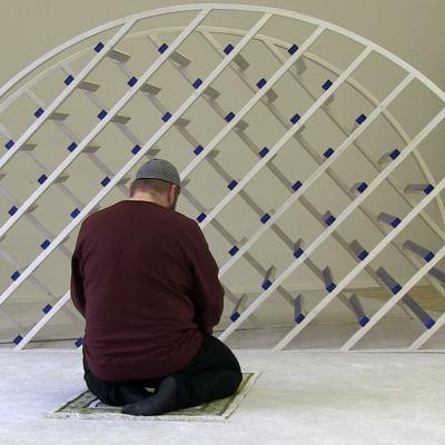 Christian Awhan Hermann sitter på en bönematta.