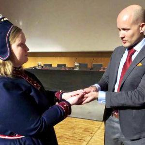 Saamelaispukuun pukeutunut nainen ja Antti Pentikäinen pitelevät luentosalissa kiveä käsissään.