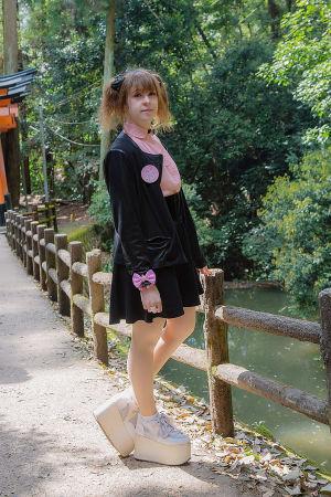 En kvinna klädd i kavaj, skjorta, kort kjol och skor med hög platåsula. Hon står vid en bro och på höger sida syns lite vatten.