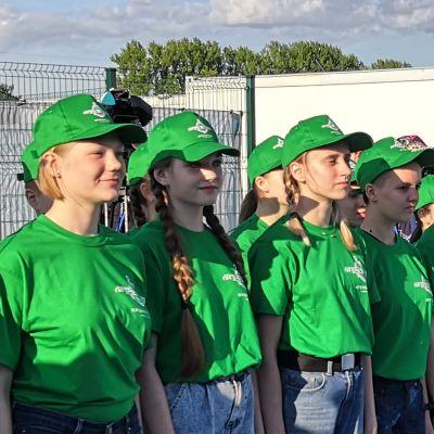 En lång rad tonårsflickor i blåa jeans och gröna t-tröjor och kepsar.
