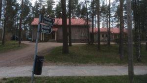 En rappad beige byggnad med rött tak skymtar bakom tallar. I förgrunden en svartvit skylt där det står Hälsogård-Terveytalo samt Bibliotek-Kirjasto.
