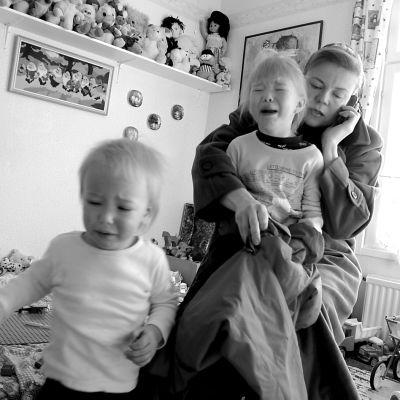 Äiti pukee itkeviä lapsiaan kiireessä