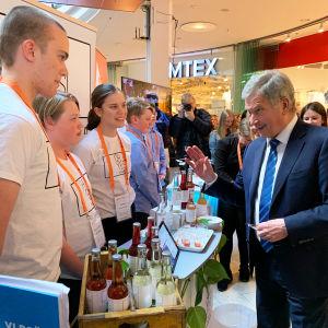 Till vänster synns tre umgdomar som står bakom ett bord med läskedrycker på. Till höger synns president Sauli Niinistö som pratar med dem.