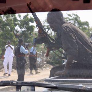 Aseistettuja miehiä auton ulkopuolella, joista yksi osoittaa pistoolilla kuvaajaa.