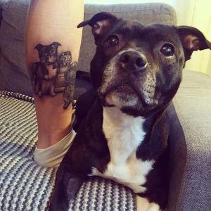 Tatuering som föreställer en hund med en äkta hund bredvid.