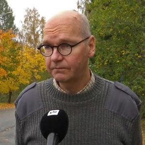 Man i grå tröja och glasögon talar i en mikrofon.