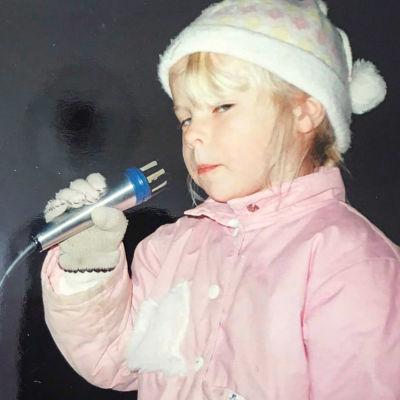Krista, 4 år gammal, håller i en mikrofon och ser stint snett in i kameran. Hon har på sig mössa och vantar.