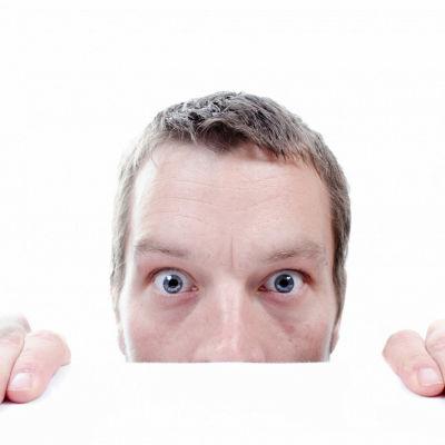 Man som förskräckt tittar fram bakom ett bord.