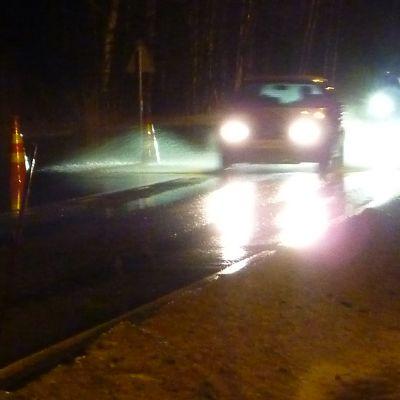 Autoilija väistää vesilammikkoa tiellä.