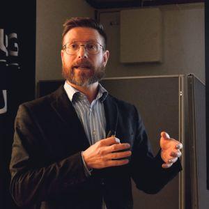 en man i kavaj och skägg håller en presentation