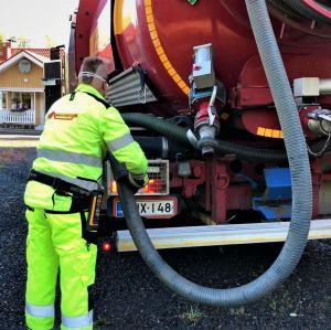 En man i arbetskläder arbetar vid en slambil.