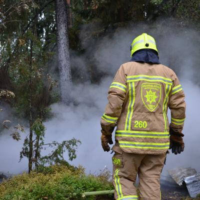En brandman i gul hjälm och beige-gul dräkt vid en skogsbrand som orsakar mycket vit rök.
