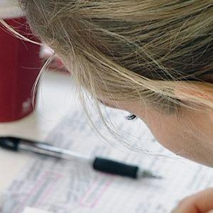 Studerande sitter böjd över papper vid ett bord